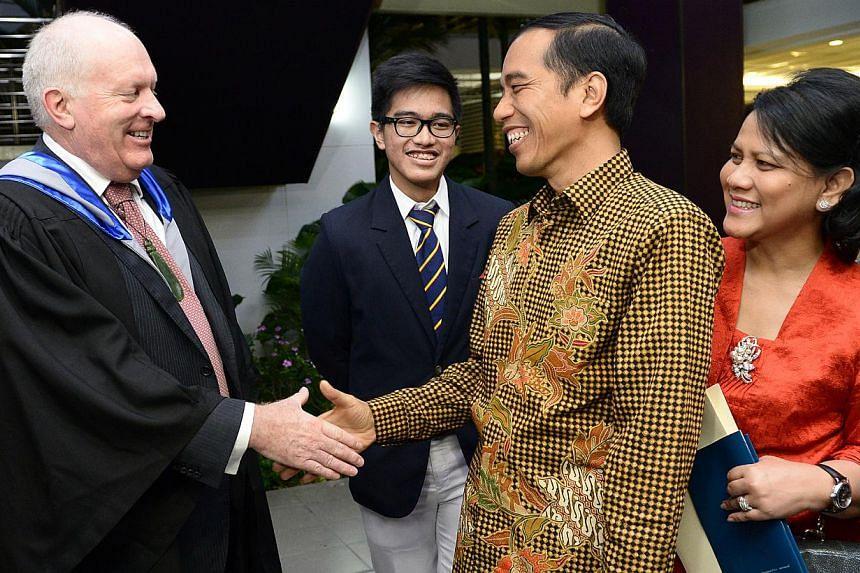 Indonesia President Joko Widodo and First Lady Iriana Widodo thank ACS (International) principal Rob Burrough (left), after the graduation ceremony. President's son Kaesang Pangarep is second from left. -- ST PHOTO: LIM SIN THAI