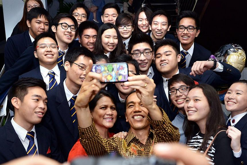 Indonesia President Joko Widodo and First Lady Iriana Widodo taking a selfie with his son Kaesang Pangarep (top right, with glasses) and his friends. -- ST PHOTO: LIM SIN THAI