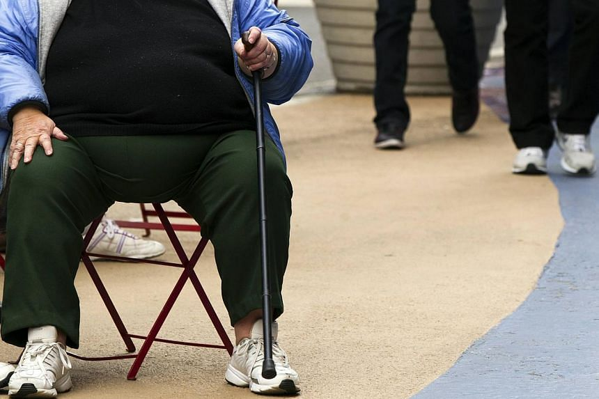 An overweight woman sits on a chair in Times Square in New York, in this May 8, 2012 file photo.More than 2.1 billion people globally, or nearly 30 per cent of the world's population, are now overweight or obese, with the figure set to ri