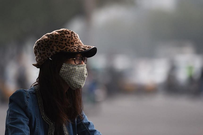 A woman wears a mask on a polluted day in Beijing in October.--PHOTO: AFP