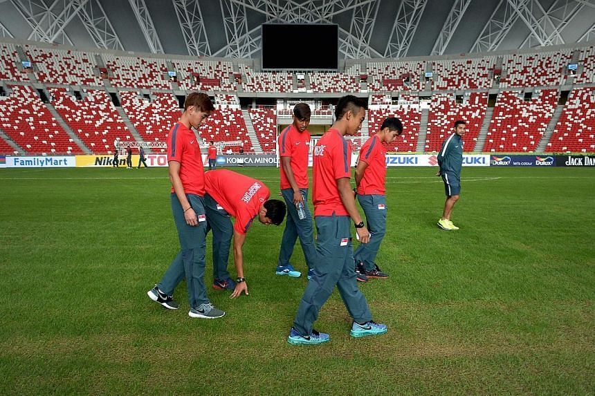 Players from the national team check the condition of the pitch at the Sports Hub.-- ST PHOTO:KUA CHEE SIONG