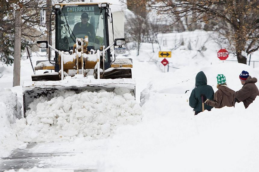 Heavy machinery clears snow from a street following an autumn storm in Buffalo, New York, Nov 20, 2014. Fresh snowstorms struck the northeastern US on Thursday, paralysing communities in a rare mid-autumn blizzard that killed eight people and dumped