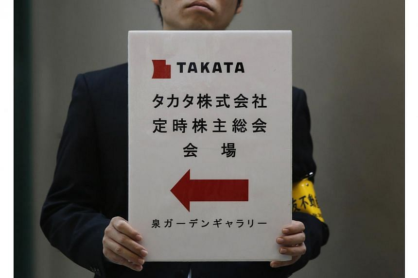 An employee of Japanese auto parts maker Takata Corp holds a sign board of the company's Annual General Meeting at an exit of a station near the venue in Tokyo on June 26, 2014. Japan's Transport Minister said on Friday that he had directed Takata Co