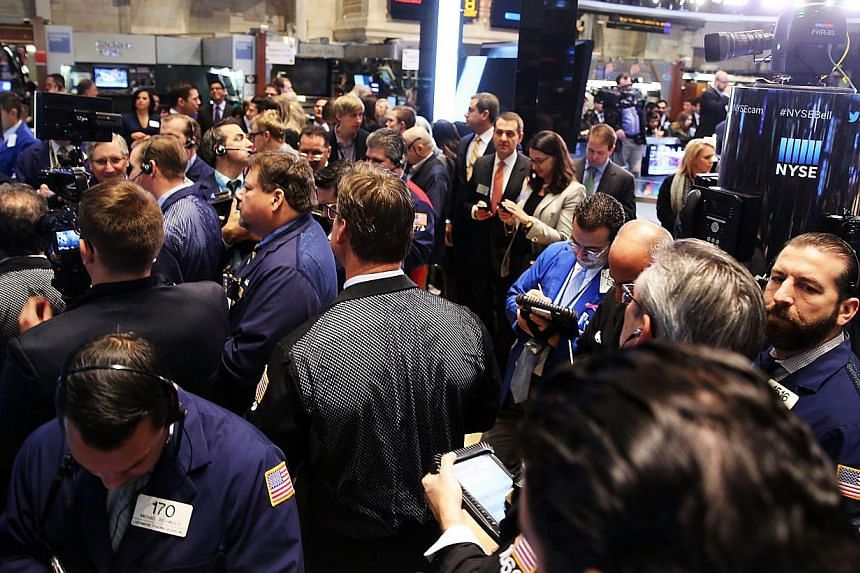 Traders on on the floor of the New York Stock Exchange on Nov 18, 2014. The Dow and S&P 500 notched fresh records Thursday on strong US economic data and a jump in oil company shares. -- PHOTO: AFP