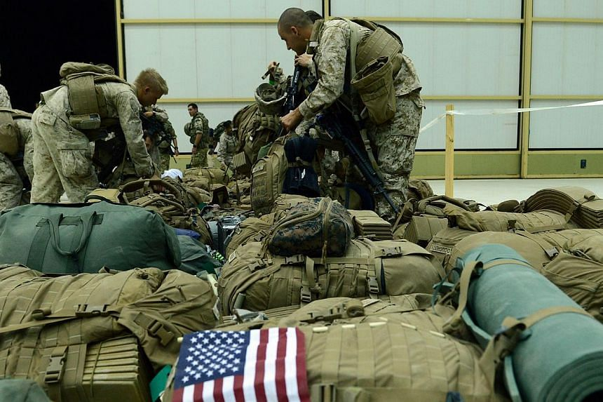 US Marines arrange their equipment in Kandahar after their withdrawal from the Camp Bastion-Leatherneck complex in Helmand province, Afghanistan, on Oct 26, 2014. -- PHOTO: AFP