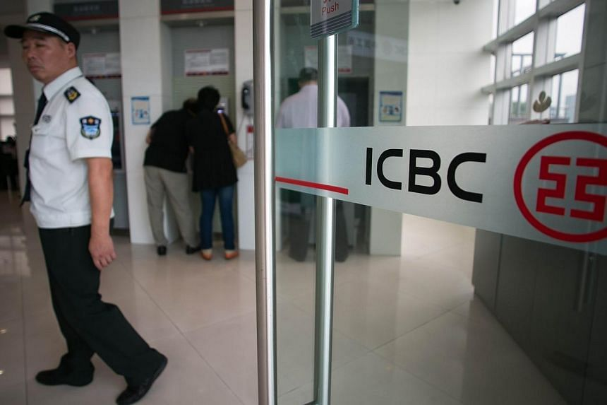 A security guard of an Industrial and Commercial Bank of China Ltd (ICBC) branch stands next to the entrance at the China (Shanghai) Pilot Free Trade zone during a media trip on Sept 24, 2014.China's Industrial and Commercial Bank (ICBC) signed