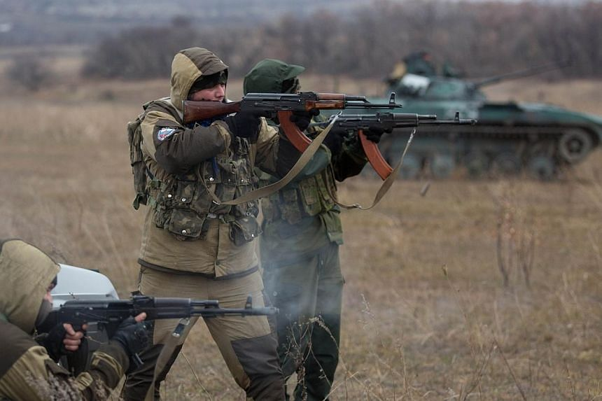 Pro-Russian militants fire their Kalachnikov asssault rifles near an tank taken from Ukrainian forces during fighting in August, as they test fire in an open field, in the eastern Ukrainian town of Ilovaisk on Nov 18, 2014. -- PHOTO: AFP