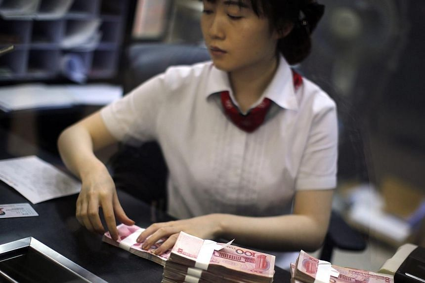 An employee of the Industrial and Commercial Bank of China Ltd (ICBC) counts money at one of the bank's branches at the Shanghai Free Trade Zone in Pudong district, in Shanghai on Sept 24, 2014. China's Industrial and Commercial Bank (ICBC) sign
