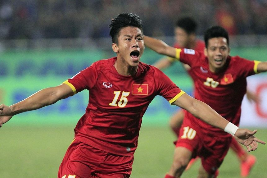 Vietnam's Que Ngoc Hai (front) celebrates with teammate Nguyen Van Quyet after scoring a goal during their Suzuki Cup match against Indonesia at My Dinh stadium in Hanoi on Nov 22, 2014. -- PHOTO: REUTERS