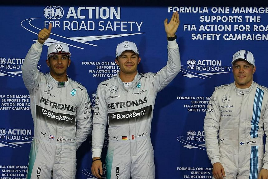 Mercedes drivers Nico Rosberg (centre) and Lewis Hamilton (left) and Williams driver Valtteri Bottas celebrate after the qualifying session at the Yas Marina circuit in Abu Dhabi on Nov 22, 2014, ahead of the Abu Dhabi Formula One Grand Prix. -- PHOT