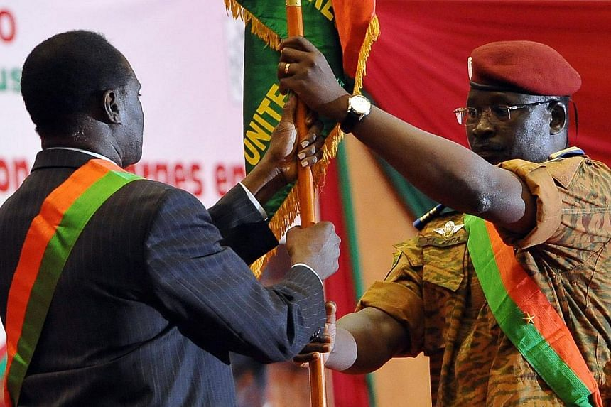 Lt-Col Isaac Zida (right) presenting the Burkinabe flag to interim civilian President Michel Kafando on Nov 21, 2014, at a stadium in Ouagadougou for a ceremony attended by six African heads of state. -- PHOTO: AFP
