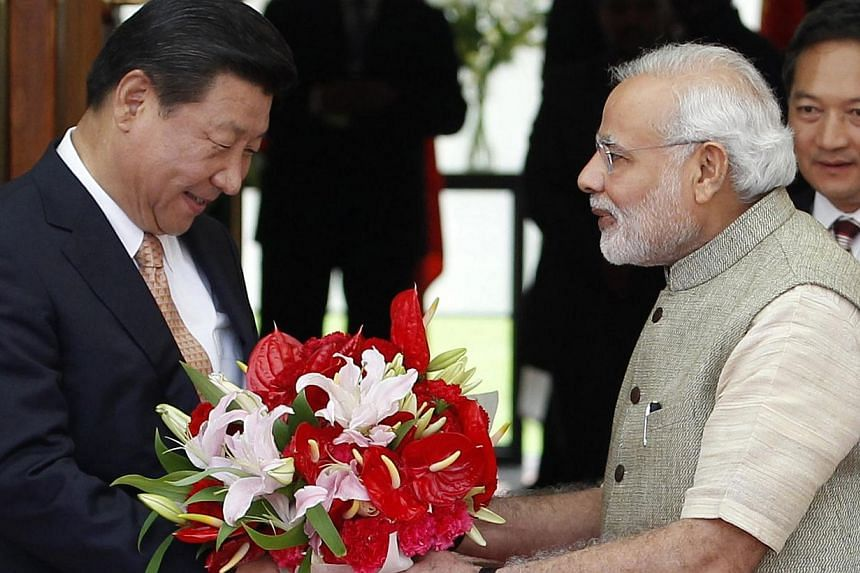 India's Prime Minister Narendra Modi presenting a bouquet to Chinese President Xi Jinping when they met in the Indian city of Ahmedabad in September. The world will look upon Mr Modi and Mr Xi to become wise statesmen and overcome the nagging border