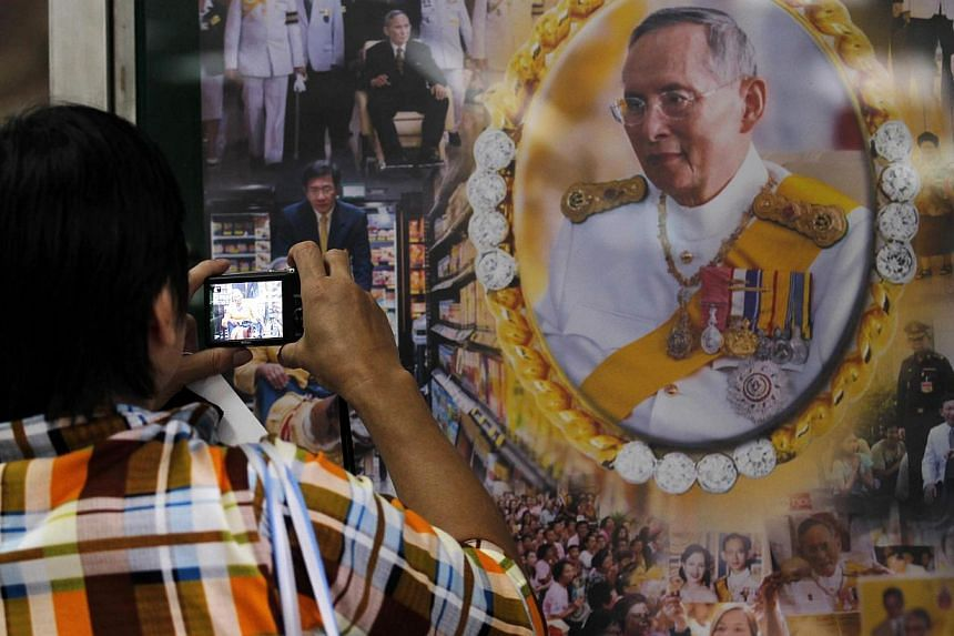 A well-wisher takes a picture of Thailand's revered King Bhumibol Adulyadej at the Siriraj hospital in Bangkok on Oct 8, 2014. The king missed a planned meeting with two government ministers, palace officials said, amid ongoing public concern over th