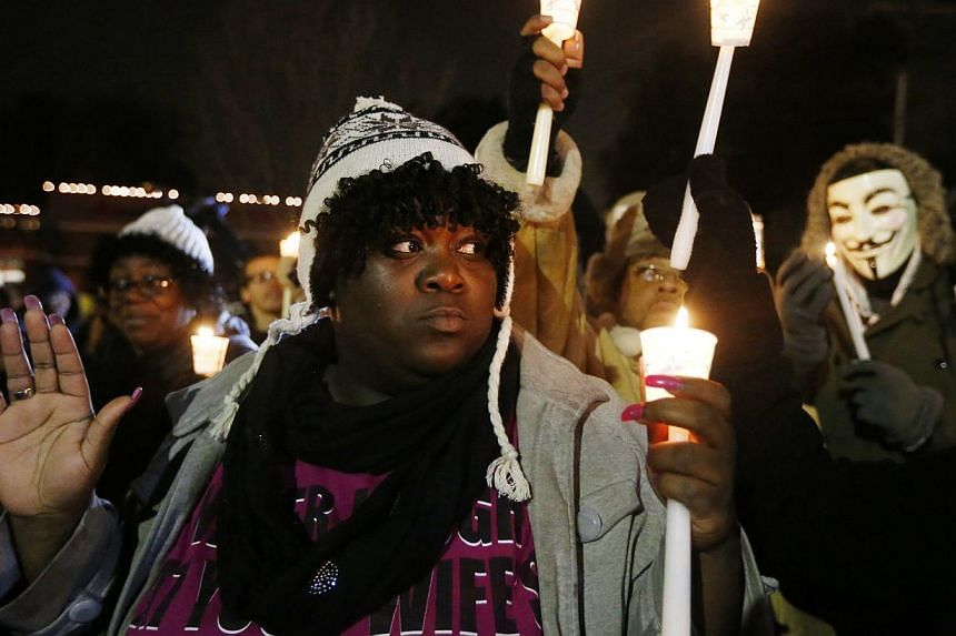 Protesters gather for a candlelight vigil over the Aug 9 police shooting of Michael Brown, outside the Ferguson Police Department in Ferguson, Missouri on Nov 21, 2014. -- PHOTO: REUTERS