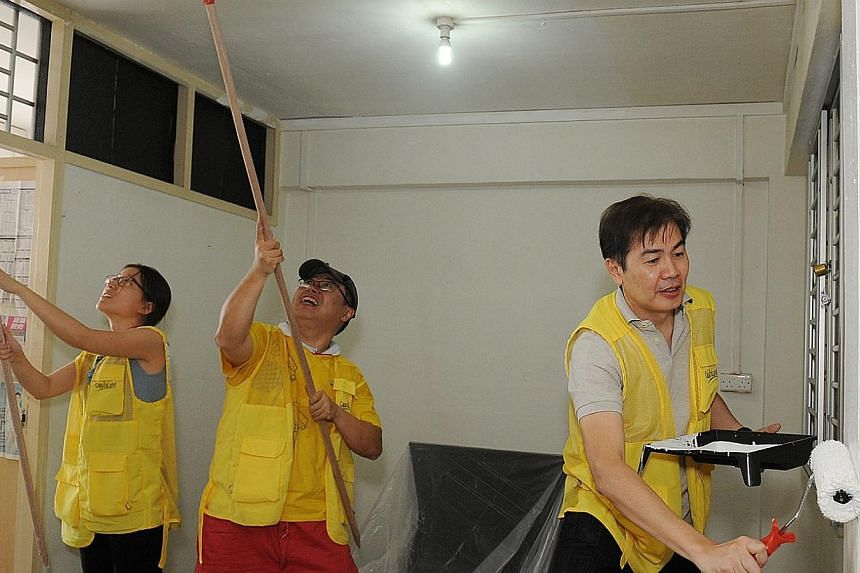 (From right) CapitaLand president Lim Ming Yan, group chief financial officer Arthur Lang, and a staff volunteer painting at a residential unit during the CapitaLand Volunteer Day on Friday. -- PHOTO: CAPITALAND