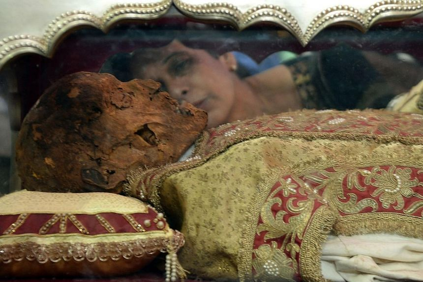 An Indian Christian kisses a casket carrying the remains of the St Francis Xavier at the Se Cathedral in Goa on Nov 22, 2014. -- PHOTO: AFP