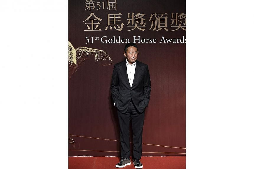 Taiwanese director Niu Chen-Zer poses for photographers on the red carpet at the 51st Golden Horse Film Awards in Taipei on Nov 22, 2014. -- PHOTO: REUTERS