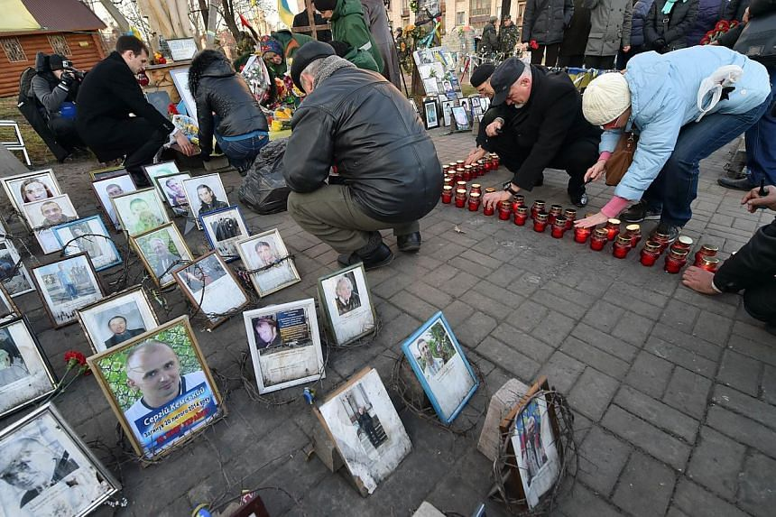 People set candles during a memorial ceremony in Kiev on Nov 21, 2014. Dozens of people gathered at the iconic Independence Square, known locally as Maidan, laying flowers at shrines to the more than 100 people who died in protests that started on No