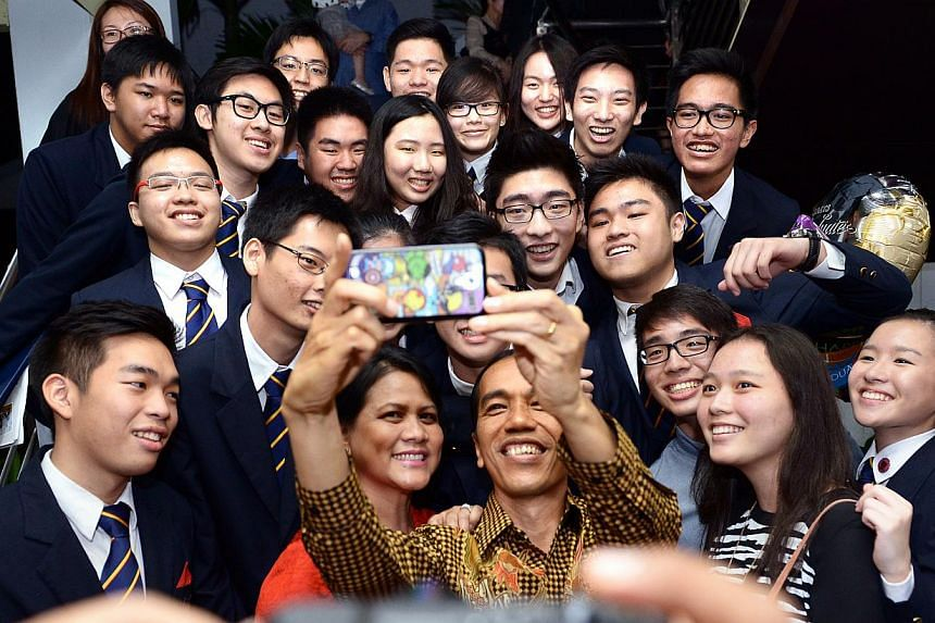 Indonesia President Joko Widodo and First Lady Iriana Widodo in a selfie with his son Kaesang Pangarep's (top right, with glasses) friends.-- ST PHOTO:LIM SIN THAI