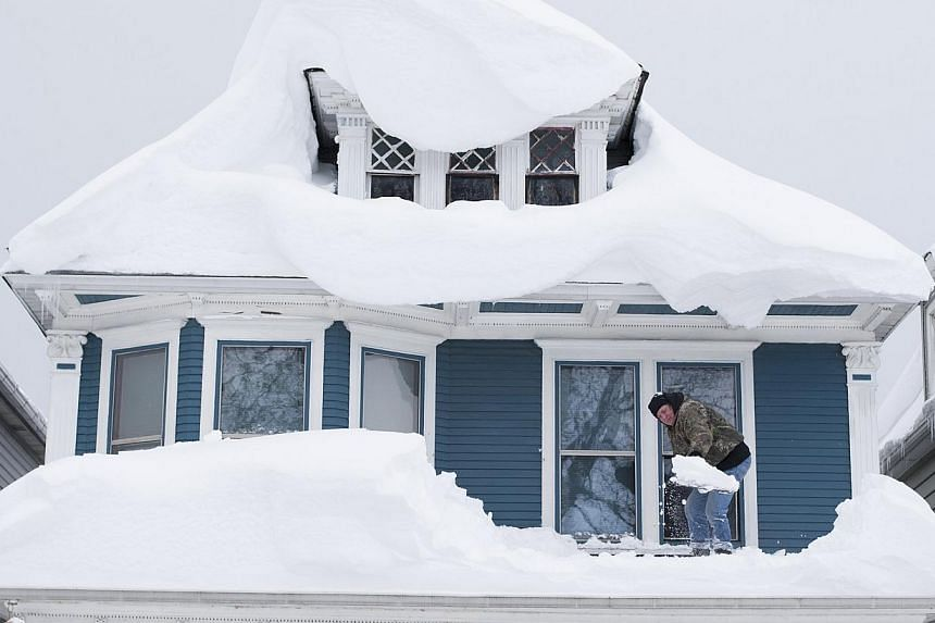 Tom Wilczak shovels snow from the roof of his home following a storm in Buffalo, New York Nov 20, 2014. The death toll rose to 13 on Friday from a rare pre-winter snowstorm in western New York state where rising temperatures and heavy weekend rain is