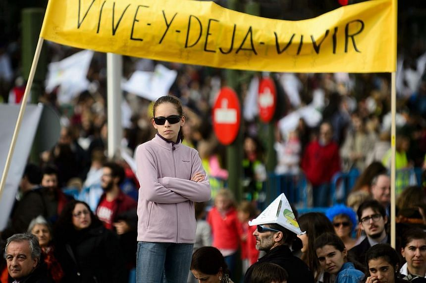 """Demonstrators hold a banner reading """"live and let live"""" during a march against abortion in Madrid on Sept 22, 2014. -- PHOTO: AFP"""