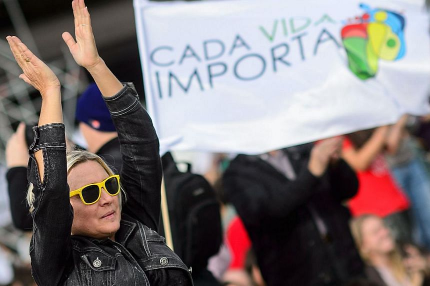 """A supporter gestures past a banner reading """"Every life matters"""" during a march against abortion in Madrid on September 22, 2014.-- PHOTO: AFP"""