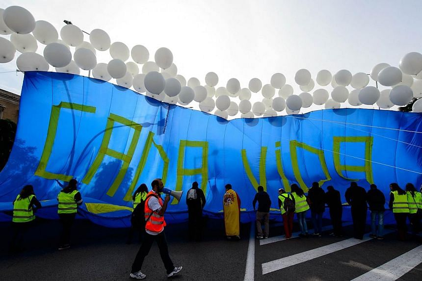 """Supporters try to display a banner with air ballons reading """"Every life matters"""" during a march against abortion in Madrid on Sept 22, 2014.-- PHOTO: AFP"""