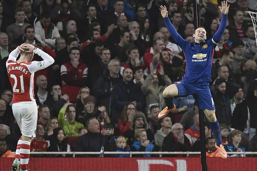 Manchester United's Wayne Rooney (right) celebrates an own goal by Arsenal's Kieran Gibbs during their English Premier League match at the Emirates Stadium in London on Nov 22, 2014. -- PHOTO: REUTERS