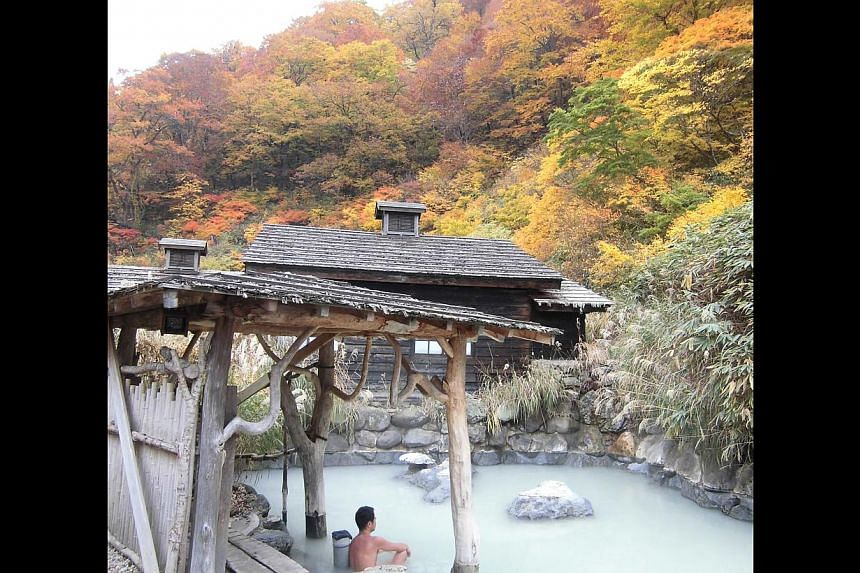 Autumn leaves (above) near the Tsurunoyu Onsen (right). Admire the view while staying warm in the waters of the Tsurunoyu Onsen. A rainbow at the Kurobe Dam (above), and the writer enjoying a meal at the Ganiba Onsen (left).