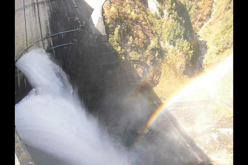 A rainbow at the Kurobe Dam (above), and the writer enjoying a meal at the Ganiba Onsen. -- ST PHOTO: GOH ENG YEOW