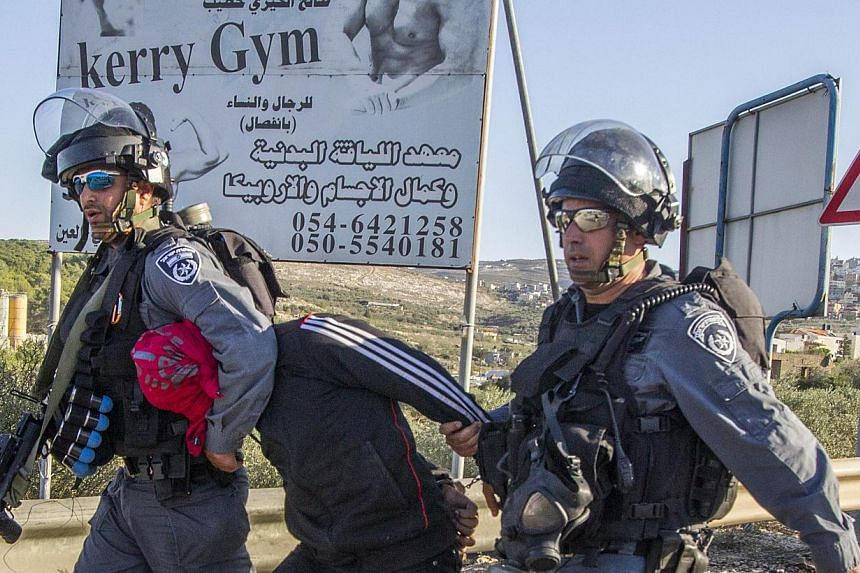Israeli security forces detain an Arab-Israeli youth during clashes in the town of Kfar Kana, in northern Israel on November 9, 2014, a day after security forces shot dead a 22-year-old Arab-Israeli man. -- PHOTO: AFP