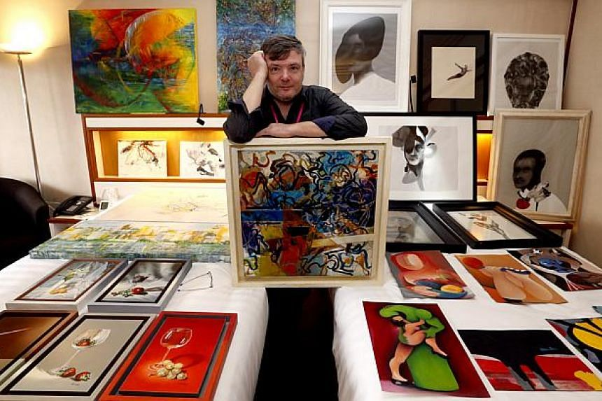 53-year-old Joaquin Balsa displays his paintings at the Bank Art Fair on the seventh and eighth floor of the Pan Pacific Hotel. -- PHOTO: CHEW SENG KIM