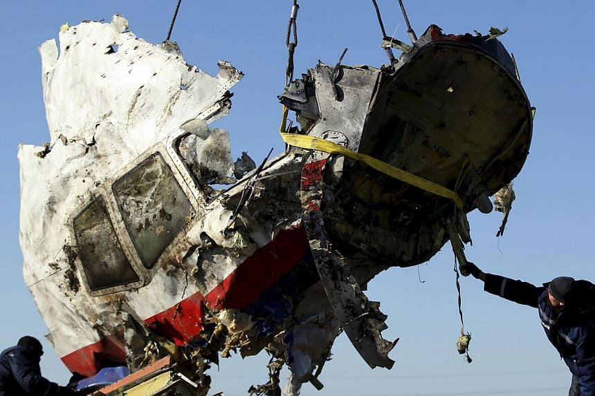 Local workers transport a piece of the Malaysia Airlines flight MH17 wreckage at the site of the plane crash near the village of Hrabove (Grabovo) in Donetsk region, eastern Ukraine on November 20, 2014. -- PHOTO: REUTERS