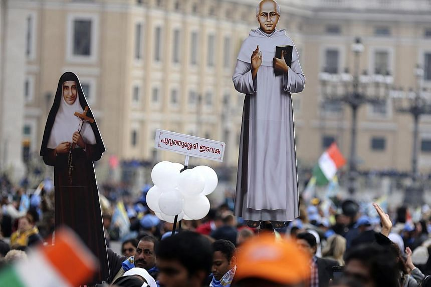 Faithful hold cut-outs of new Indian saints Kuriakose Elias Chavara (right) and Mother Euphrasia Eluvathingal before a canonisation ceremony led by Pope Francis, to make saints out of six men and women, in Saint Peter's square at the Vatican on Novem