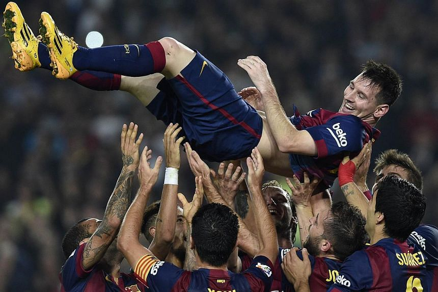 Barcelona's Argentinian forward Lionel Messi (top) is thrown into the air by his teammates as they celebrate his new record after he scored during the Spanish league football match FC Barcelona versus Sevilla FC at the Camp Nou stadium in Barcelona o