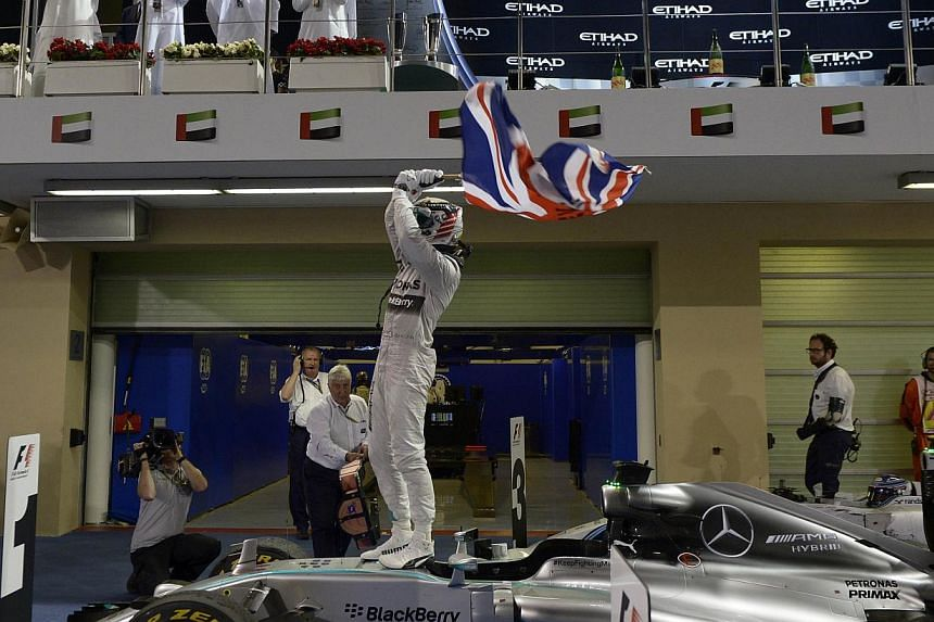 Mercedes' British driver Lewis Hamilton waves his country's flag in triumph at the Yas Marina circuit in Abu Dhabi on November 23, 2014 after winning the Abu Dhabi Formula One Grand Prix.