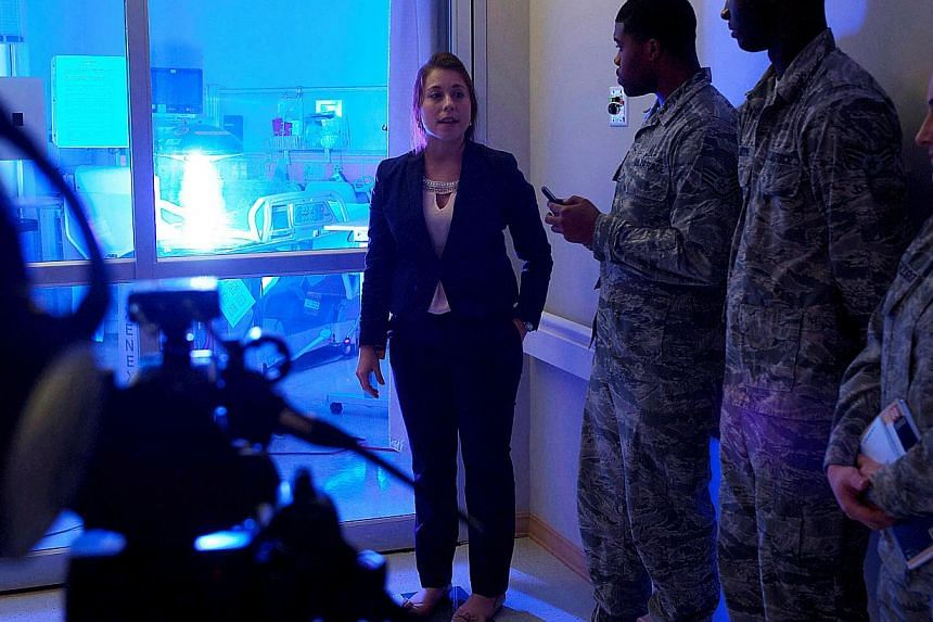 """This US Air Force photo obtained on November 22, 2014 shows Geri Genant (left), as she demonstrates the capabilities of """"Saul"""", a germ-zapping robot, to airmen in this October 20, 2014 photo, at Joint Base Langley-Eustis, Virginia. -- PHOTO: AFP"""