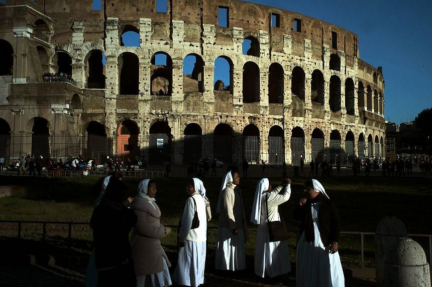 Nuns take pictures of the Colosseum at sunset on Nov 21, 2014 in Rome. A Russian tourist caught red-handed trying to carve his initials on a wall of Rome's Colosseum was ordered Saturday to pay a fine of €20,000 (S$32,200), Ansa reported. -- PHOTO: