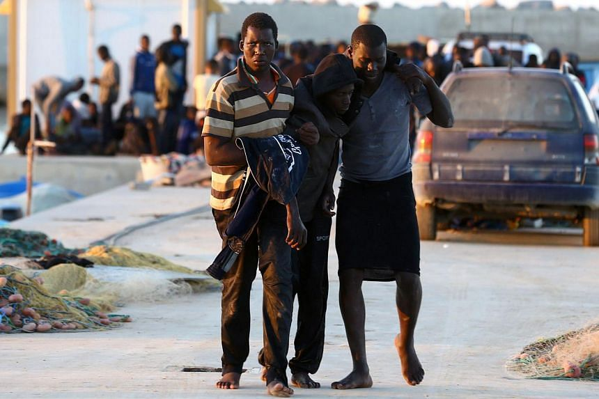 Sub-Saharan African migrants arrive in the coastal town of Guarabouli, 60 kilometres east of the capital Tripoli after they were rescued by the Libyan coastguard after their inflatable boat stated to sink in the waters near the town on Nov 20, 2014.