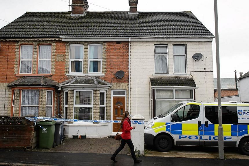 A pedestrian walks past a residential address marked off by police tape in High Wycombe, Buckinghamshire, north west of London, on November 8, 2014, in connection with the arrest of four anti-terror suspects. -- PHOTO: AFP