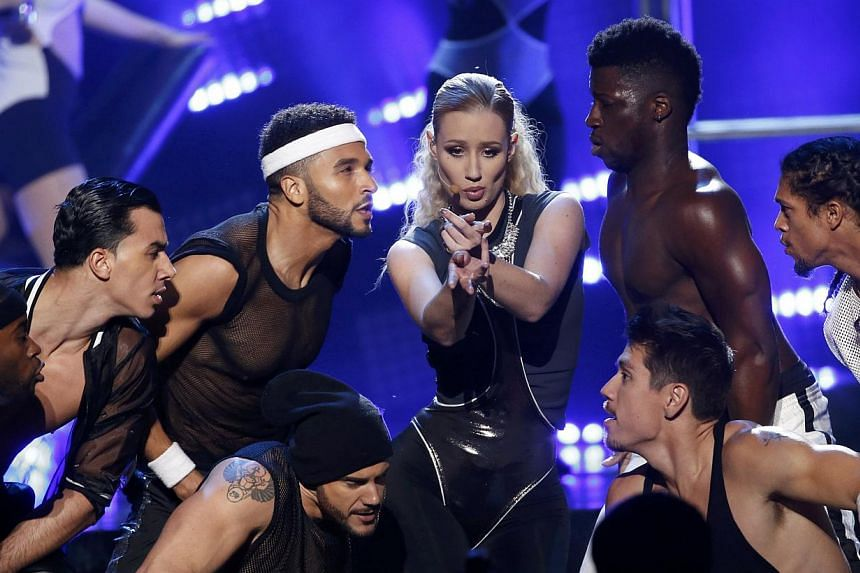 Iggy Azalea (centre) performs Beg For It during the 42nd American Music Awards in Los Angeles, California on Nov 23, 2014. -- PHOTO: REUTERS