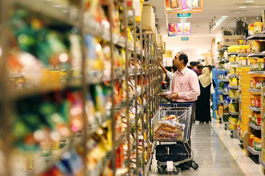 Shoppers perusing products on the shelves of Mustafa Centre's supermarket. The Singapore Consumer Price Index for October will be released on Nov 24, 2014, at 1pm. -- PHOTO: ST FILE