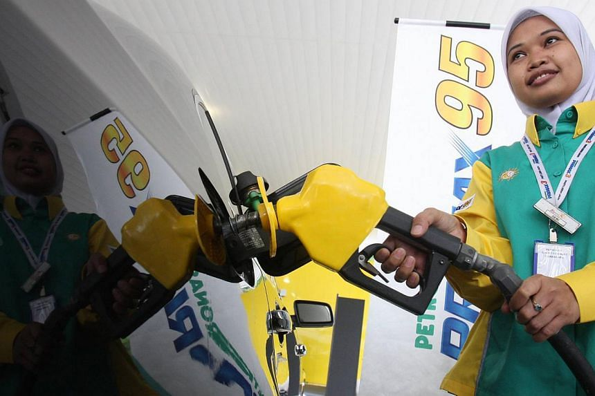 A pump attendant filling up a car with RON 95 at a Petronas station in Malaysia. -- PHOTO: THE STAR