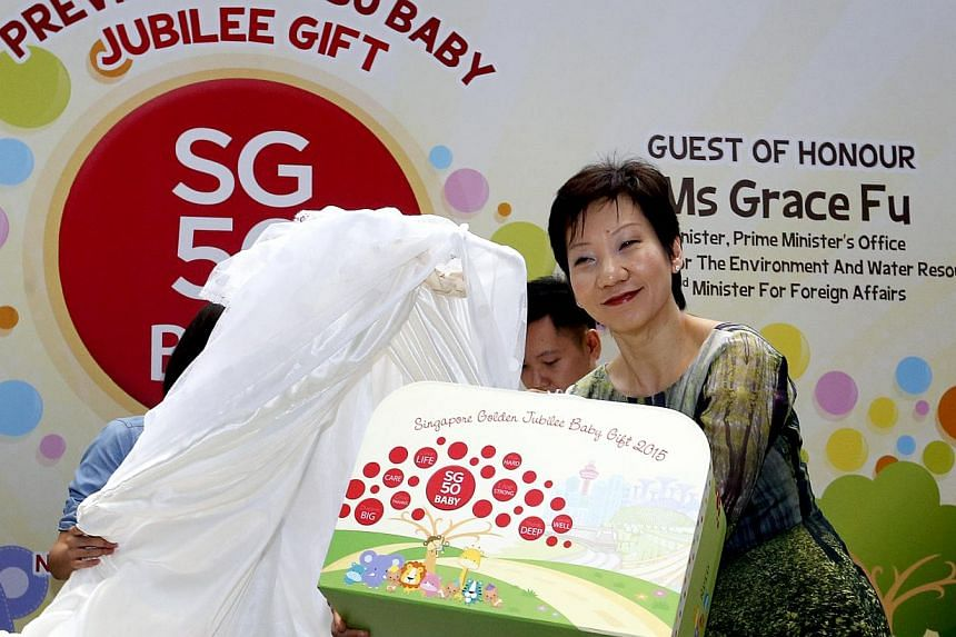Minister in the Prime Ministers Office, Grace Fu unveiling the contents of the SG50Baby Jubilee Gift at a year-end gathering of about 200 Singaporean family partners. -- ST PHOTO: CHEW SENG KIM