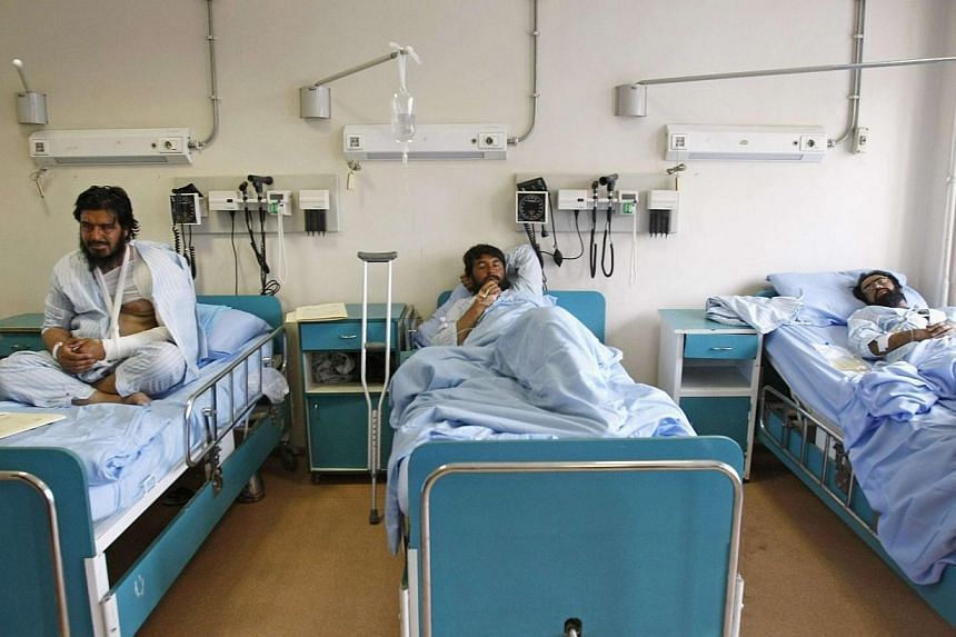 Men receive treatment at a military hospital in Kabul, after being wounded during a suicide attack at a volleyball match on Sunday in the Yahya Khail district of Paktika province, on Nov 24, 2014. Paktika provincial spokesman Mukhlis Afghan said in a