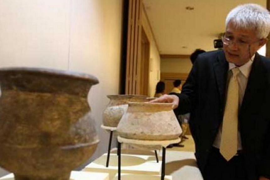 Somchai na Nakhonphanom, archaeology expert from the Fine Arts Department looks at the returned artefacts.-- PHOTO:THE NATION/ASIA NEWS NETWORK