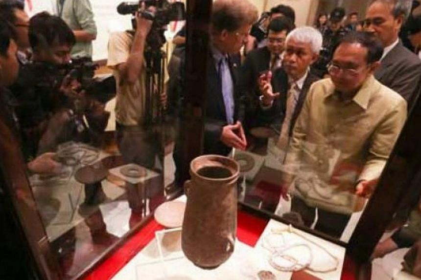 Thai and US officers look at the returned artifacts.-- PHOTO:THE NATION/ASIA NEWS NETWORK