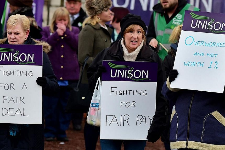 Health workers demonstrate as they take part in a four-hour strike outside the Manchester Royal Infirmary in north-west England on Nov 24, 2014. -- PHOTO: AFP