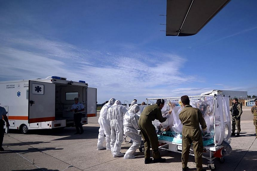 Italian aeronautical personnel wearing protective suits take care of a pretended Ebola victim during a specialized training course for the management and transport of highly contagious patients, in Rome's Pratica di Mare military airport in Pomezia.