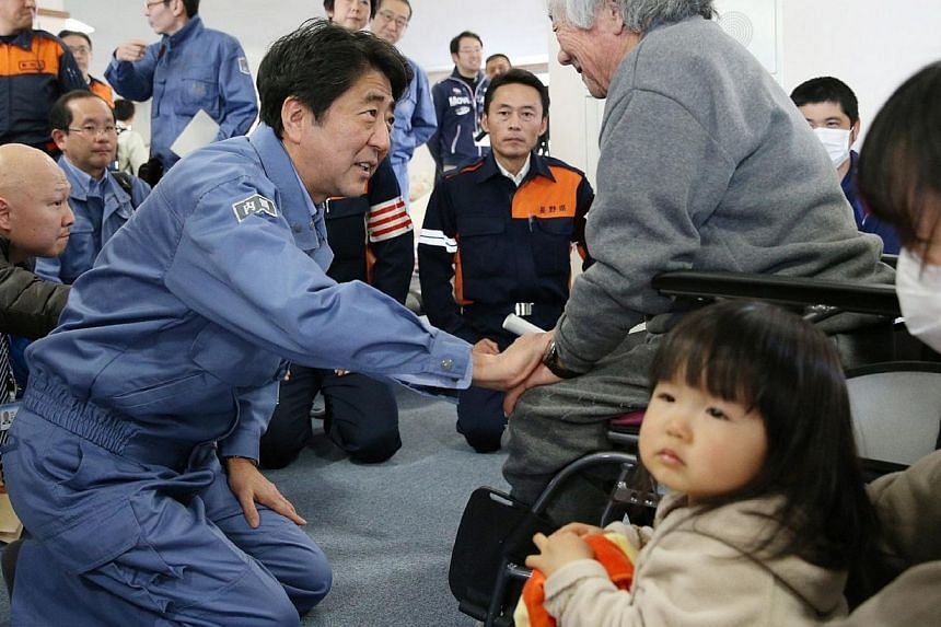 """Japanese Prime Minister Shinzo Abe (left) expresses sympathy to victims of earthquake as he visits a shelter at Hakuba village in Nagano prefecture, central Japan on Nov 24, 2014.Mr Abe on Monday promised """"firm"""" support after meeting victims of"""